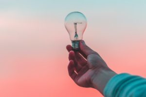 A white person's hand holds up an unlit lightbulb to the sky, which is a mixture of pink and blue shades