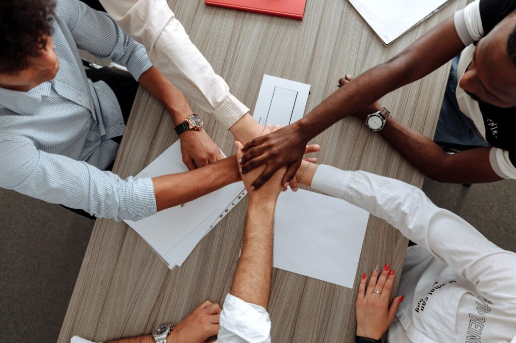 A top-down view of 5 people in smart attire sit around a table. Each of them has placed a hand in a pile in the middle