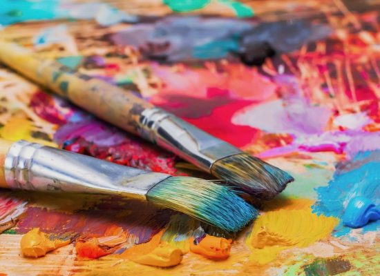Used brushes on an artist's palette of colorful oil paint for drawing and painting